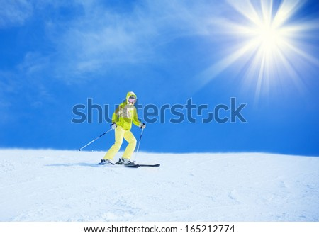 Happy young woman skier in bright clothes going downhill with clean background - stock photo