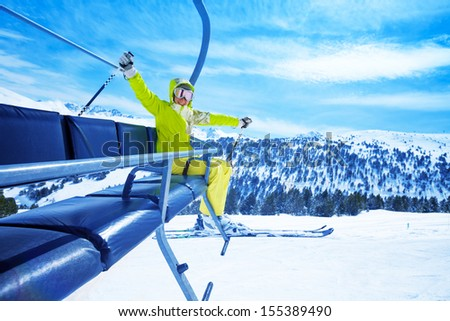 Happy young woman skier on ski lift smiling and cheerfully lifting her hands - stock photo