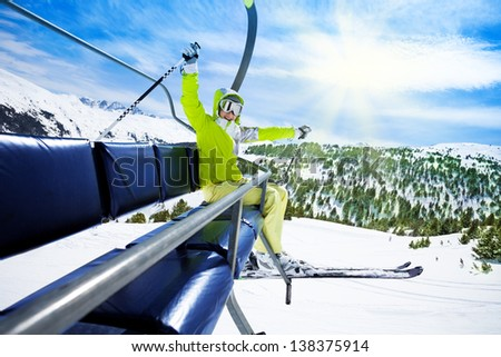 Happy young woman skier on ski lift with smile and lifted happy hands - stock photo