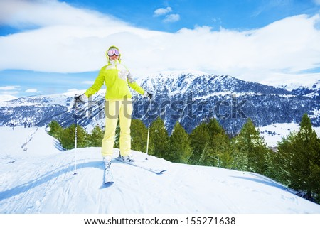 Happy young woman skier stand on the piste slope with mountain and forest on background - stock photo