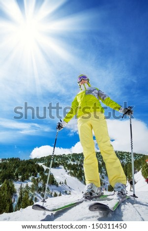 Happy young woman skier stand on top of the mountain - stock photo