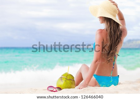 Happy young woman smiling in straw hat with closed eyes on the beach - stock photo