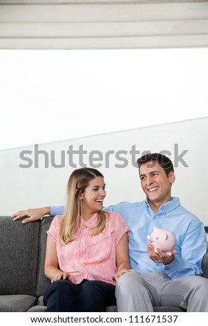 Happy young woman smiling while man holding a piggybank