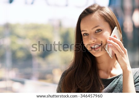 Happy young  woman speaking by cellphone indoor. Attractive caucasian girl with mobile phone in the shop. - stock photo
