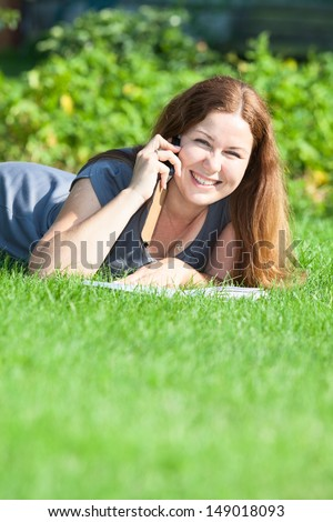 Happy young woman speaking on the phone on green grass meadow. Copyspace