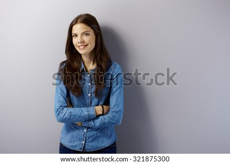 Happy young woman standing arms crossed by grey wall, looking at camera.
