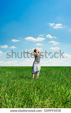 happy young woman standing at the meadow - stock photo