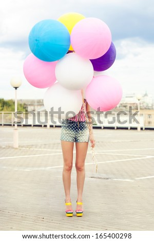 Happy young woman standing behind big colorful latex balloons. Outdoors, lifestyle - stock photo