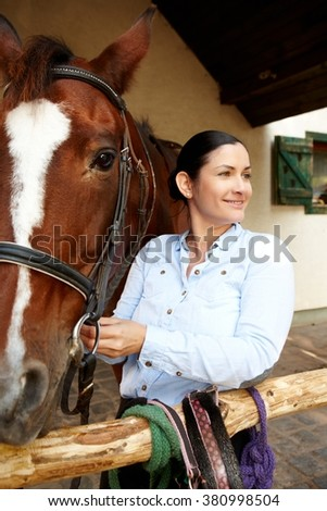 Happy young woman standing by horse, smiling, looking away. - stock photo