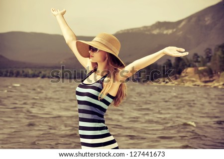 Happy young woman standing face to the wind over beautiful landscape.
