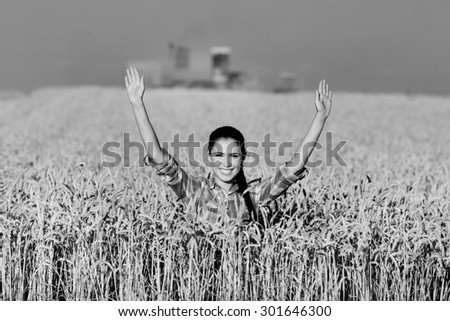 Happy young woman standing in ripe wheat field during harvest, black and white image - stock photo
