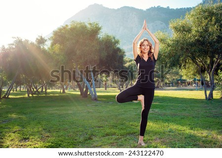 Happy young woman standing in yoga pose on the grass in the park. Practicing yoga with trees, mountains and sun ray in the background - stock photo