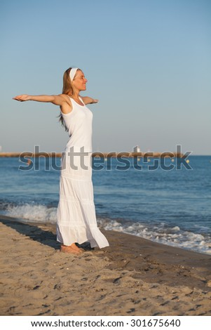 Happy young woman standing on the beach with arms outstretched - stock photo