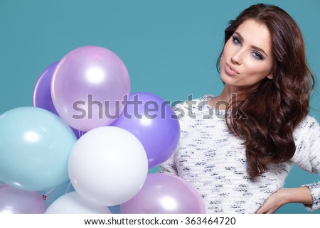 Happy young woman standing over blue wall and holding pink and white balloons. - stock photo