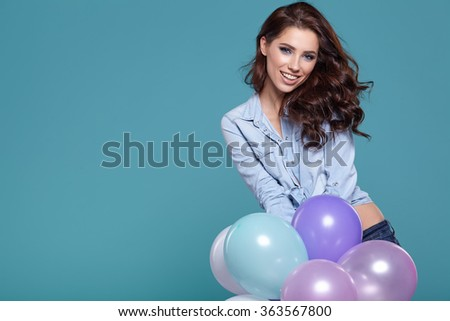 Happy young woman standing over blue wall and holding pink and white balloons. Pleasure. Dreams. Toned.