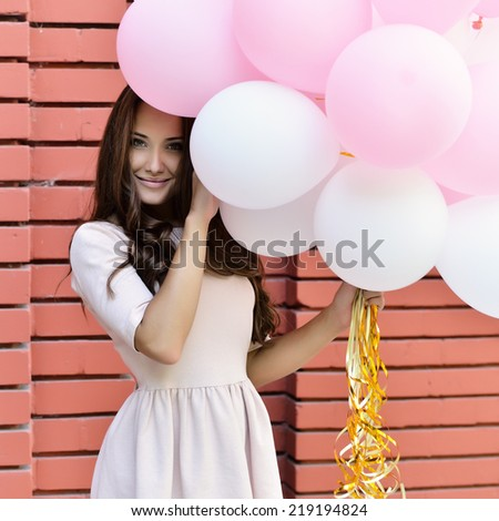happy young woman standing over red brick wall and holding pink and white balloons - stock photo