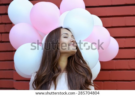 Happy young woman standing over red brick wall and holding pink and white balloons. Pleasure. Dreams. - stock photo