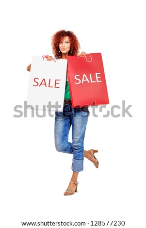 Happy young woman standing with shopping bags. Isolated over white.