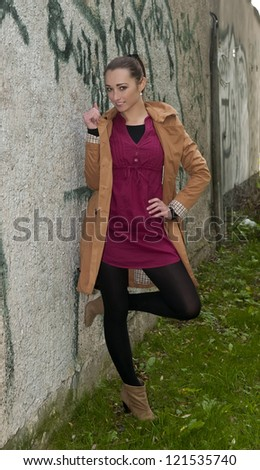 happy young woman stands on a wall