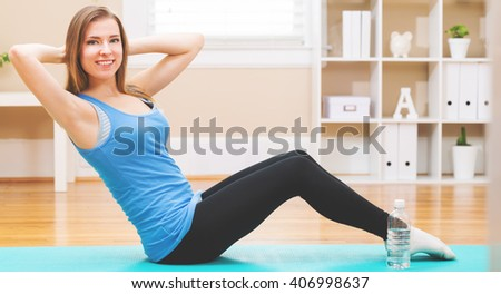 Happy young woman stretching in a her home studio