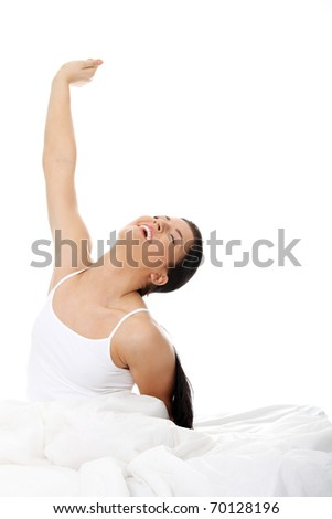 Happy young woman stretching in bed, isolated on white