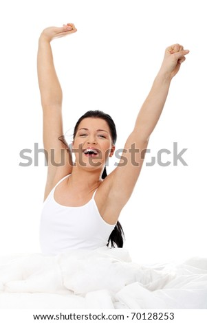 Happy young woman stretching in bed, isolated on white - stock photo