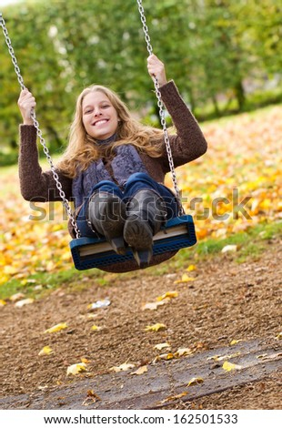 Happy, young woman swinging