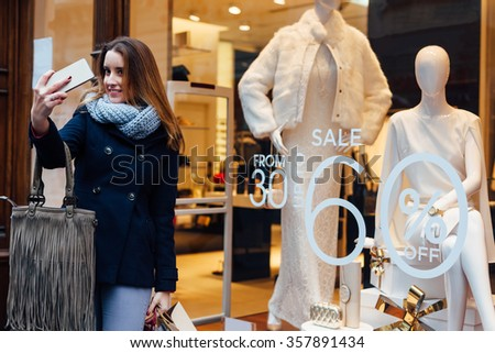 Happy young woman taking self portrait after shopping - stock photo