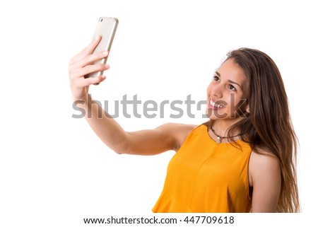 Happy young woman taking self portrait photography through smart phone over white background. - stock photo