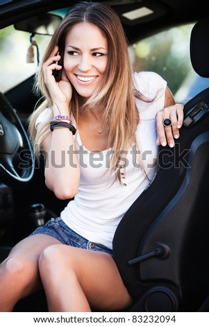 happy young woman talk on cell phone sitting in car