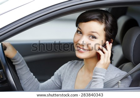 happy young woman talk on cell phone sitting in white car