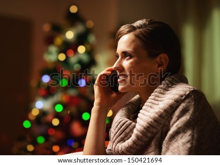 Happy young woman talking cell phone in front of christmas tree - stock photo