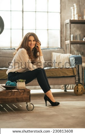 Happy young woman talking cell phone while sitting in loft apartment