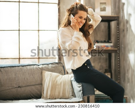 Happy young woman talking mobile phone in loft apartment - stock photo