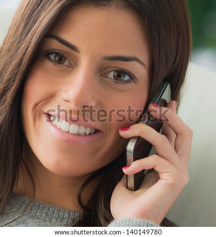 Happy Young Woman Talking On Cell Phone, Indoors - stock photo