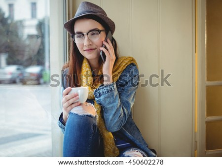 Happy young woman talking on mobile phone at cafe