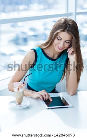 happy young woman talking on the cell phone and using tablet computer in a coffee shop