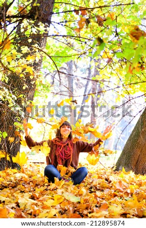 Happy young woman throwing autumn leaves in park. - stock photo