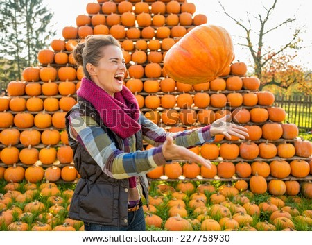 Happy young woman throwing pumpkin in front of pumpkin rows