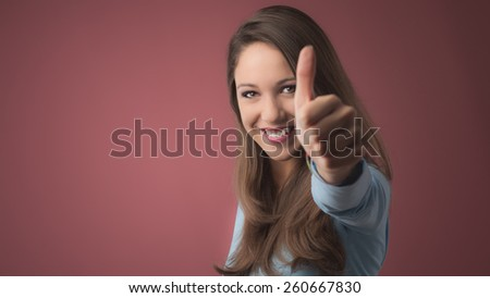 Happy young woman thumbs up smiling at camera - stock photo