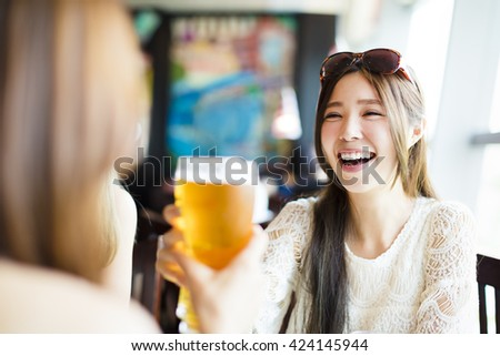 happy young woman toasting and drinking in the  restaurant