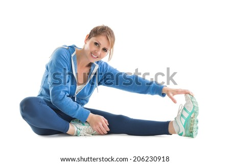 Happy young woman touching hand to leg over white background