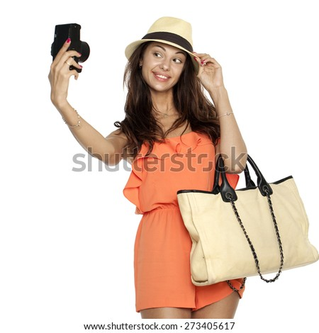 Happy young woman using a camera to take photo, isolated on white