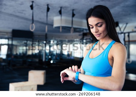 Happy young woman using activity tracker in fitness gym  - stock photo