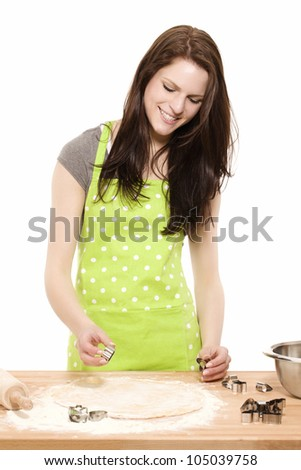 happy young woman using christmas molds on dough in front of white background - stock photo