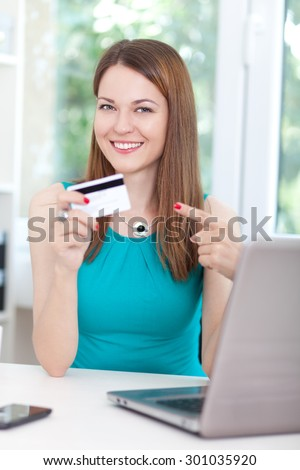 Happy young woman using her credit card for online shopping