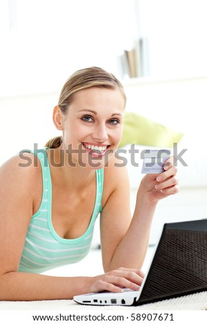 Happy young woman using her laptop holding a card in the living room - stock photo