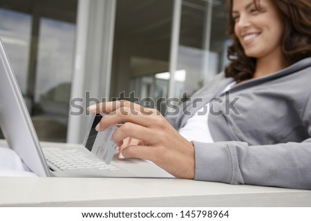 Happy young woman using laptop and credit card on porch - stock photo