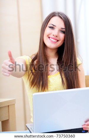 Happy young woman using laptop at home and giving thumb-up gesture to you