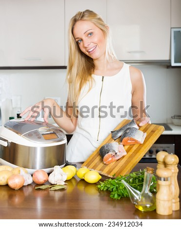 Happy young woman using new  slo-cooker at home - stock photo